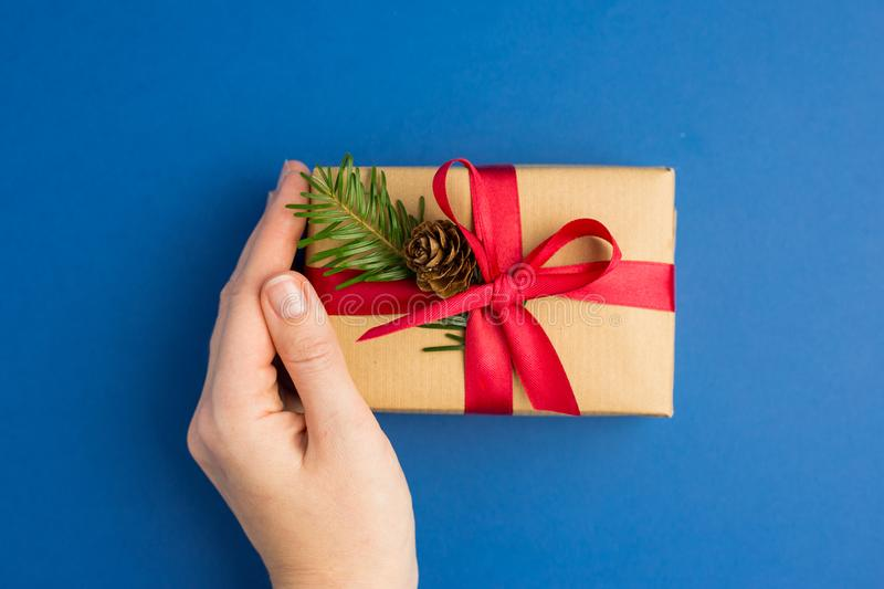 Brown gift boxes with red ribbons and fir tree branch on blue trendy background. Woman hand holding present for Christmas box. royalty free stock image