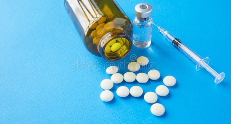 Brown-Glasflasche mit weißen Pillen und eine Spritze mit einer pharmazeutischen Vorbereitung auf dem Tisch lizenzfreies stockfoto