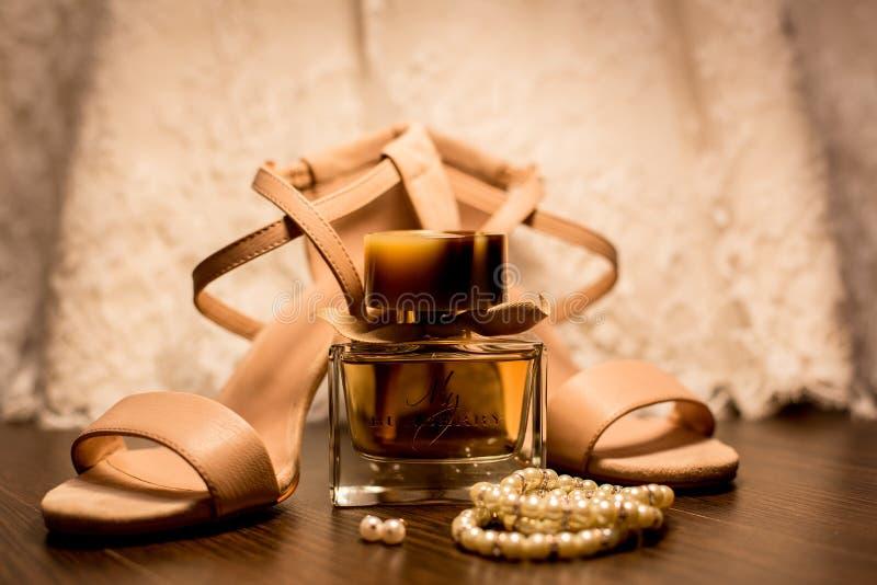 Brown Glass Fragrance Bottle Beside White Pearl Bracelets stock photo