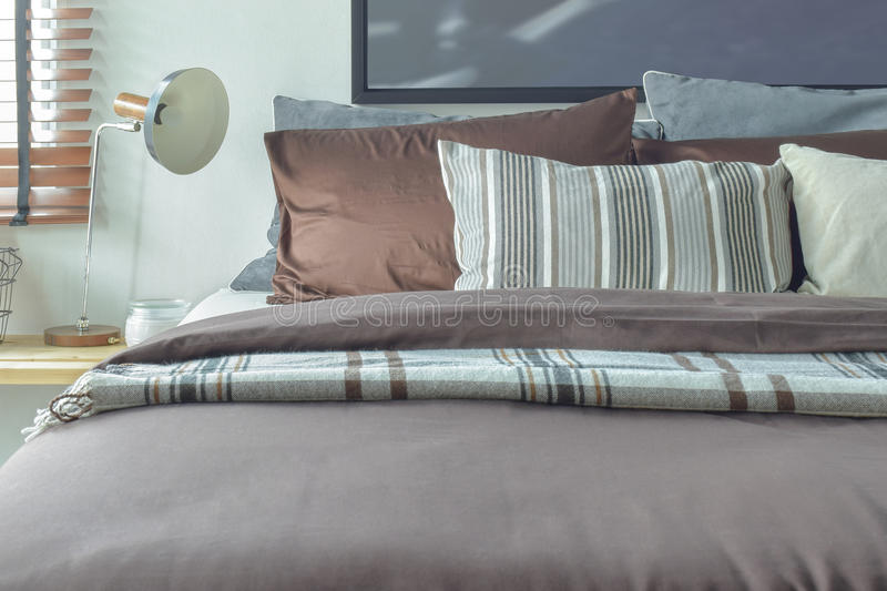 Brown and gray color scheme bedding with reading lamp. Brown and gray scheme bedding with reading lamp royalty free stock photos