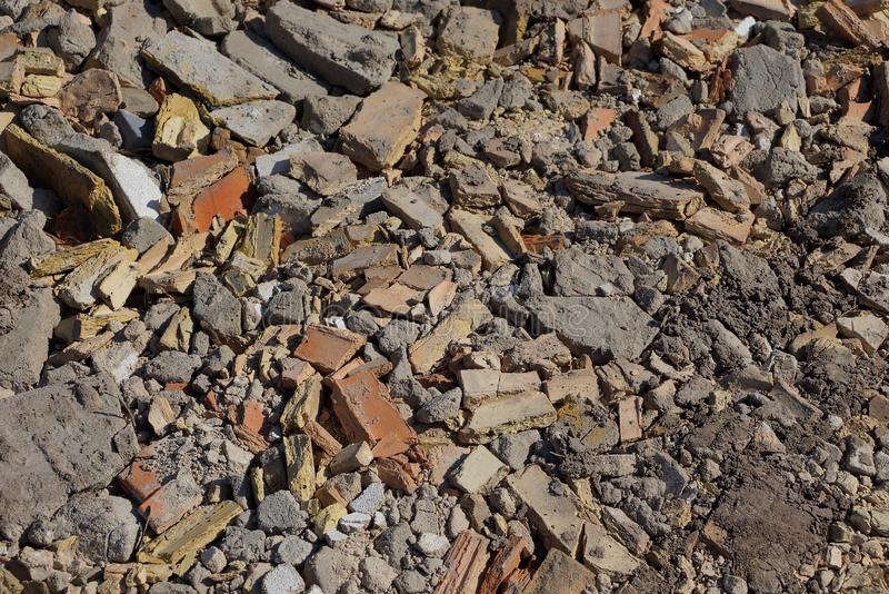 Brown gray stone texture from pieces of bricks and concrete in a pile of garbage on the street. Brown gray stone background from pieces of bricks and concrete in royalty free stock photos