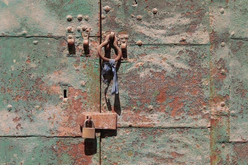 Brown green rusty old door handle and padlock. Valletta, Malta royalty free stock photo