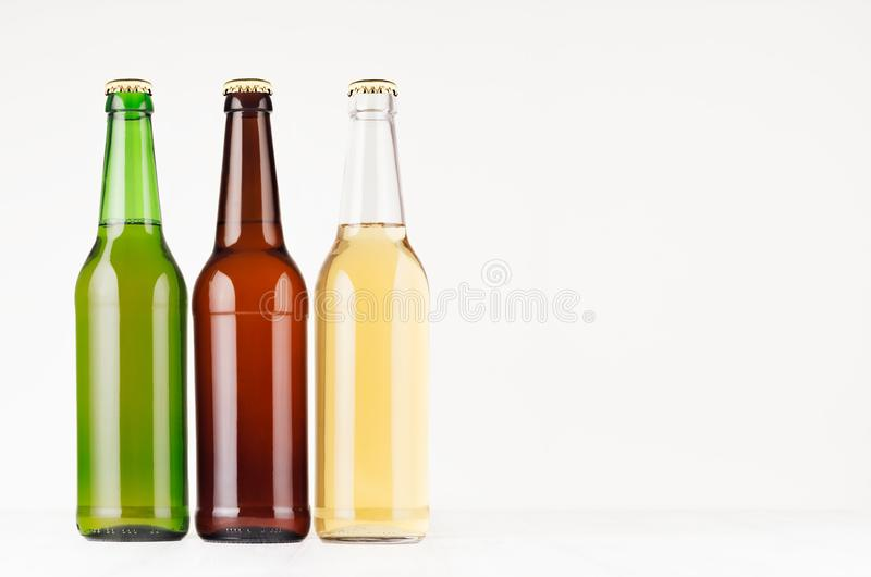 Brown, green, transparent longneck beer bottles 500ml, mock up. Template for advertising, design, branding identity on white wood. Table royalty free stock photos