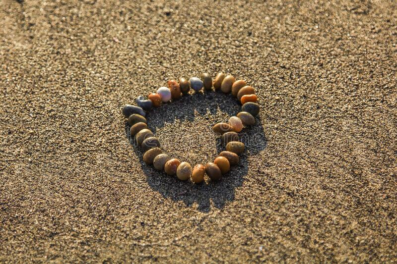 Brown and Grey Stone Formed Heart on Sand stock image