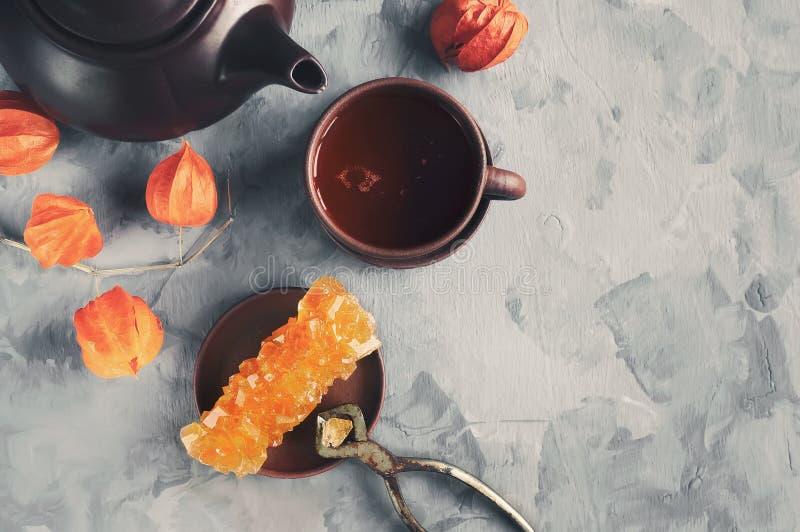 Brown Gronowy cukier w jasnych kryształach, herbacie i tongs na popielatym łupkowym zakończeniu, Orientalna słodkość herbata Odbi obrazy royalty free