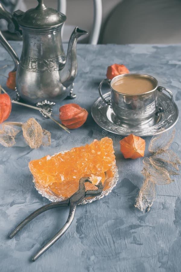 Brown Gronowy cukier w jasnych kryształach, herbacie i tongs na popielatym łupkowym zakończeniu, Orientalna słodkość herbata fotografia royalty free
