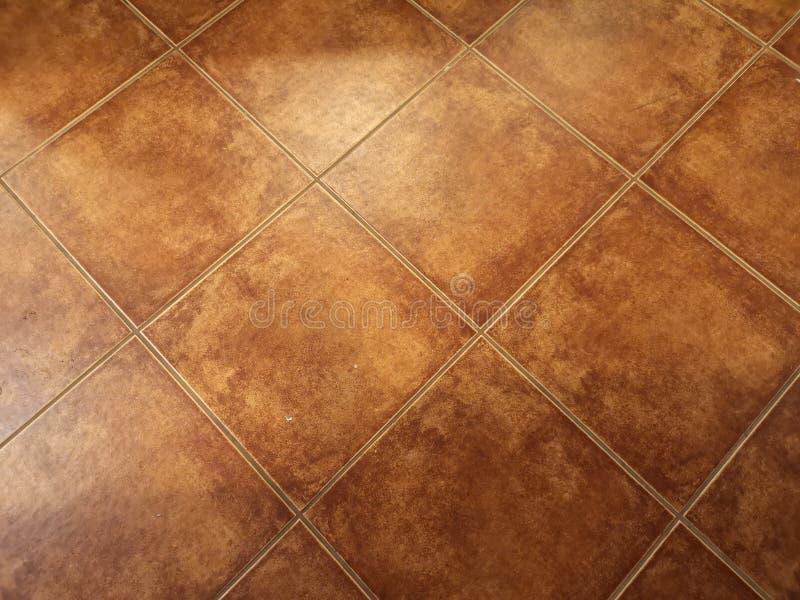 Brown ha lustrato le mattonelle struttura il pavimento materiale immagini stock libere da diritti