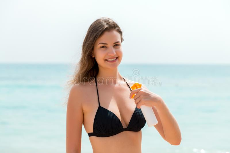 Brown hair woman is applying sunsceen from the spray on her body at the sea background.  stock images
