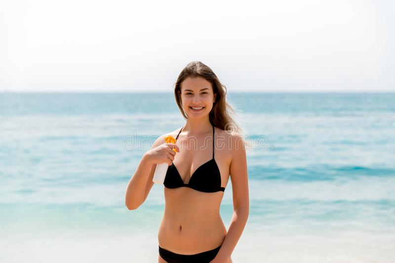 Brown hair woman is applying sunsceen from the spray on her body at the sea background.  royalty free stock photo