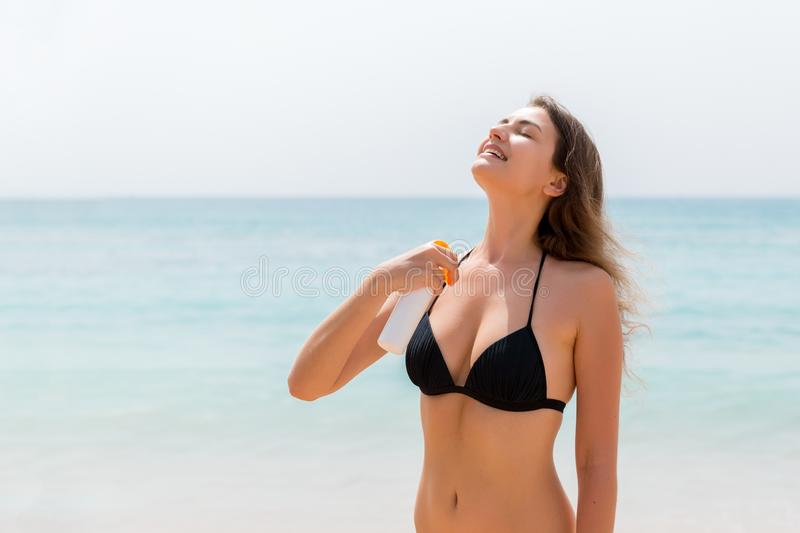 Brown hair woman is applying sunsceen from the spray on her body at the sea background.  royalty free stock image