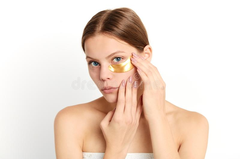 Brown-haire woman sticking gold collagen crystal anti-wrinkle under eye royalty free stock photography
