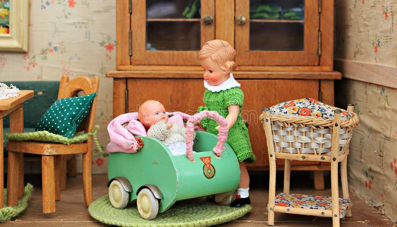 Brown Haired Girl Doll Holding Baby in Bassinet Doll royalty free stock photo