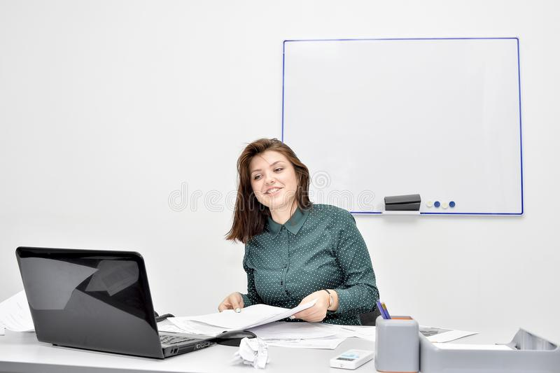 The brown-haired girl in front of the laptop screen happily talks on Skype. The concept of distance learning. stock image