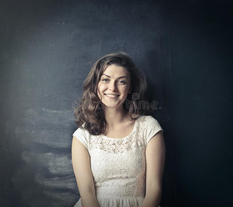 Brown Haired Girl in White Sleeveless Dress Standing Beside Black Painted Wall royalty free stock photos