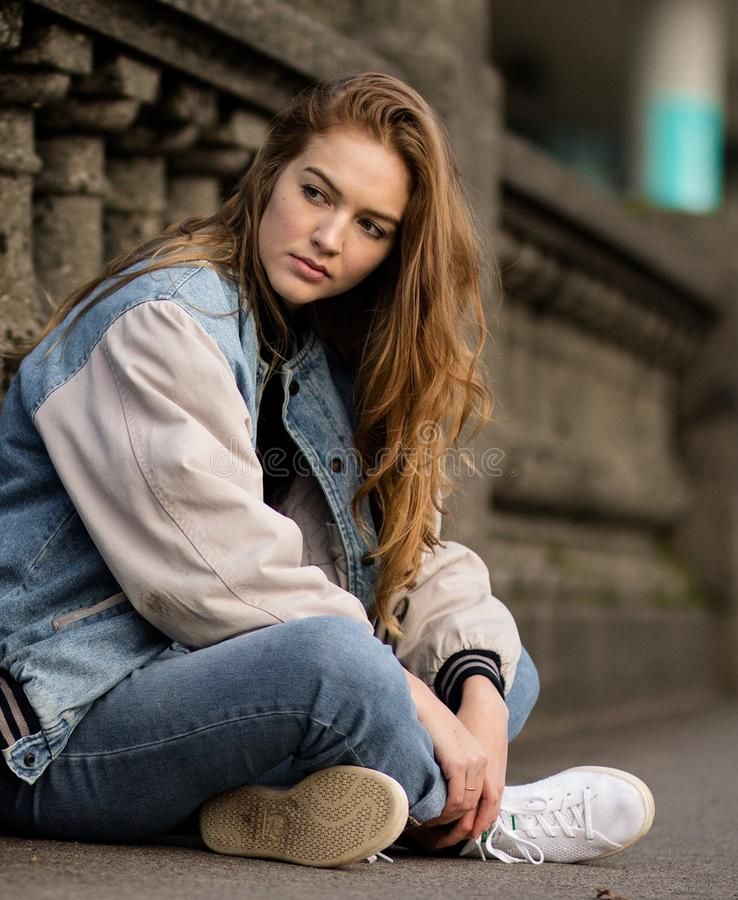 Brown Haired Woman Sitting Beside Gray Concrete Railings stock image