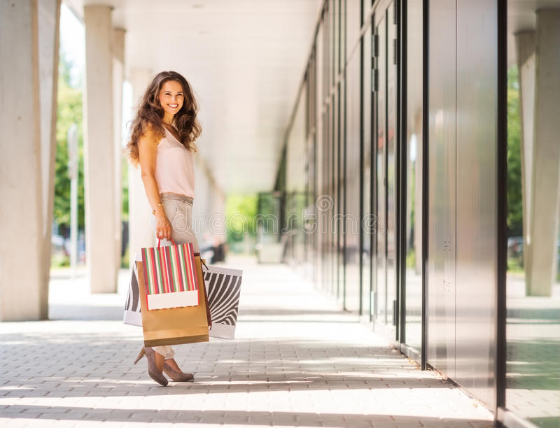 Brown-haired woman smiling holding colourful shopping bags royalty free stock image