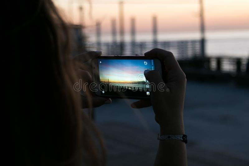 Brown Haired Woman Taking a Photo of Sunset royalty free stock photos