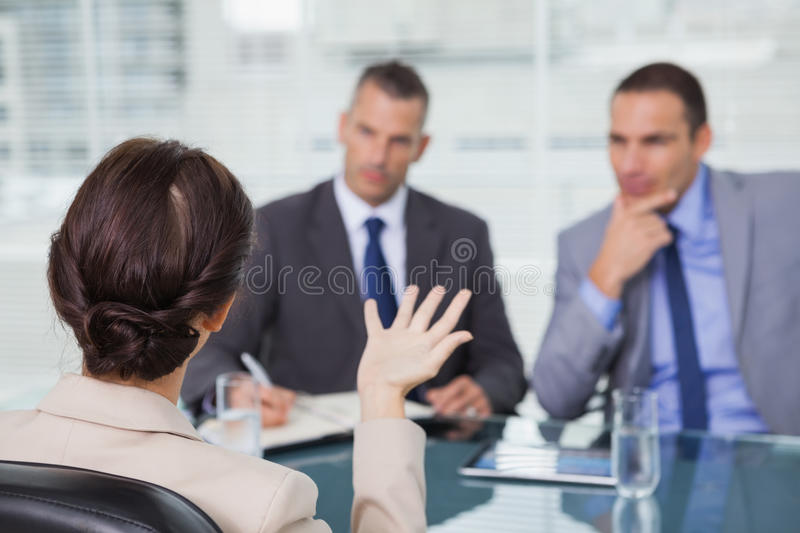 Brown haired woman talking to her interviewers royalty free stock image