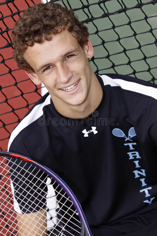 Brown haired young man smiling with tennis racket stock image
