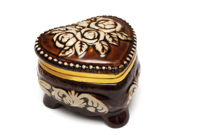 A brown heart shaped jewel box with flower carvings stock photography