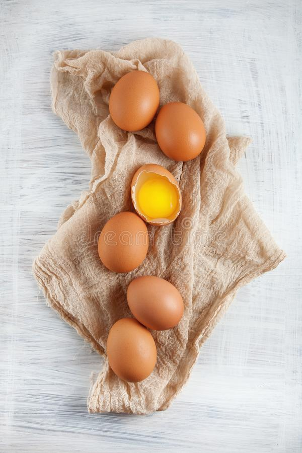Brown hen`s eggs one egg yolk visible decorated on napkin stock photography