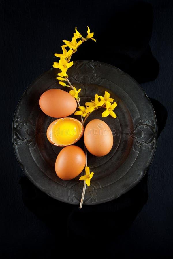 Brown-Henne ` s Eier verziert mit gelben Blumen auf antiker Platte, rustikale Lebensmittelphotographie stockbilder