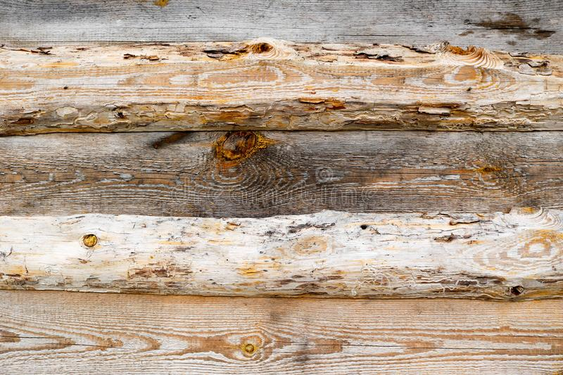 Brown horizontal texture of wooden logs, boards with knots, cracks and beautiful patterns of wood fibers stock image