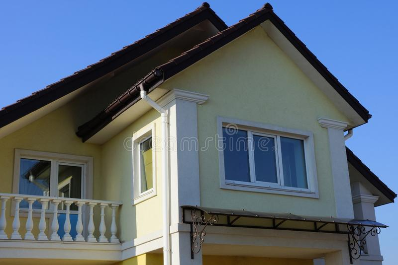 Brown house facade with windows and a white balcony against the sky. Brown house facade with windows and a white balcony against a blue sky royalty free stock photo