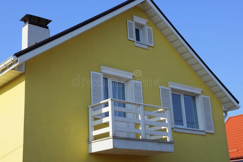 Brown house facade with windows and a white wooden balcony against the sky. Brown house facade with windows and a white wooden balcony against a blue sky stock image