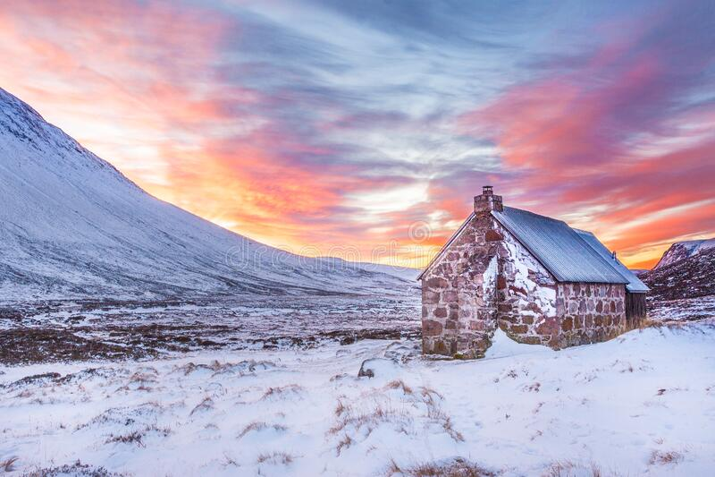 Brown House Surrounded by Snow Covered Field Near Snow Covered Mountain Under Yellow Blue and Orange Sunset royalty free stock photos