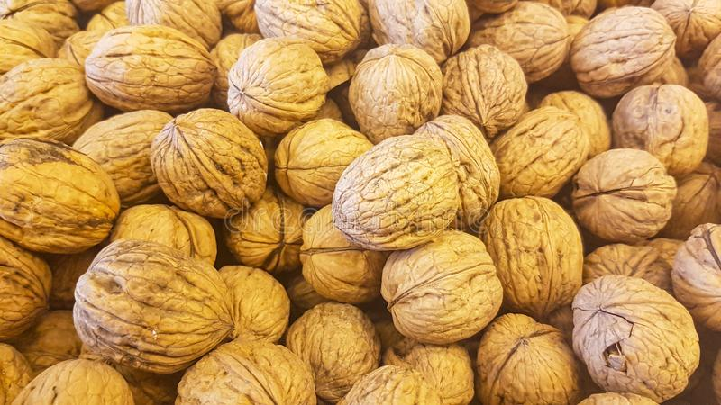 Brown inshell walnuts in the fresh vegan market. Lots of brown inshell walnuts texture at the fresh vegan market stock photos
