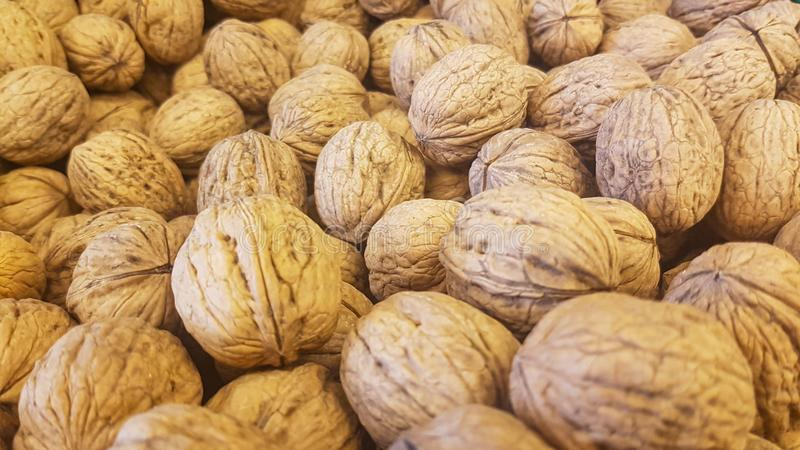 Brown inshell walnuts in the fresh vegan market. Lots of brown inshell walnuts texture at the fresh vegan market royalty free stock photos