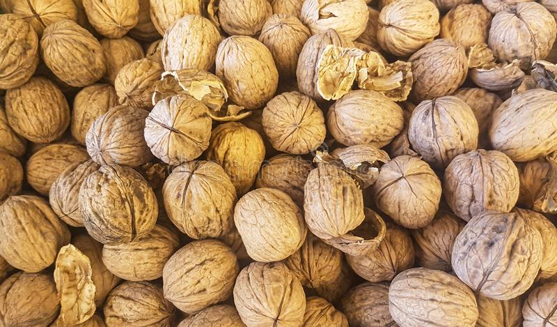 Brown inshell walnuts in the fresh vegan market. Lots of brown inshell walnuts texture at the fresh vegan market royalty free stock images