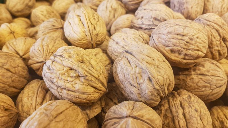 Brown inshell walnuts in the fresh vegan market. Lots of brown inshell walnuts texture at the fresh vegan market stock photo