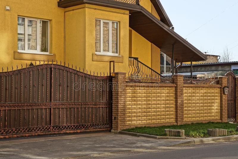 Brown iron gate and a brick fence in the street in front of the house royalty free stock image