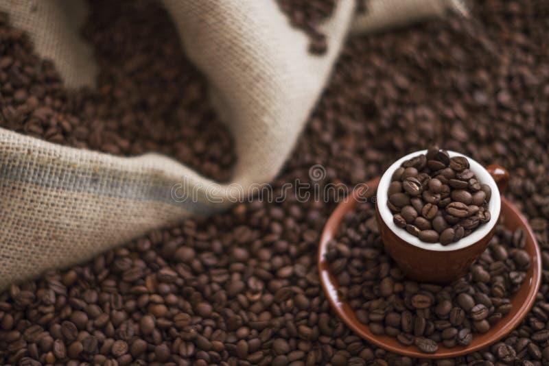 Brown-Kaffeetasse- und Röstkaffeebohnen auf Holztisch mit Sack im Hintergrund stockbild