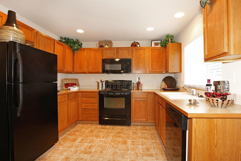 Brown Kitchen Cabinets With Black Appliances Stock Image - Image of ...