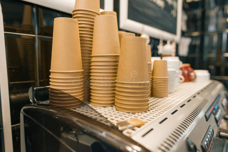Brown kraft paper coffee cups close-up on coffee machine in coffee shop interior royalty free stock images