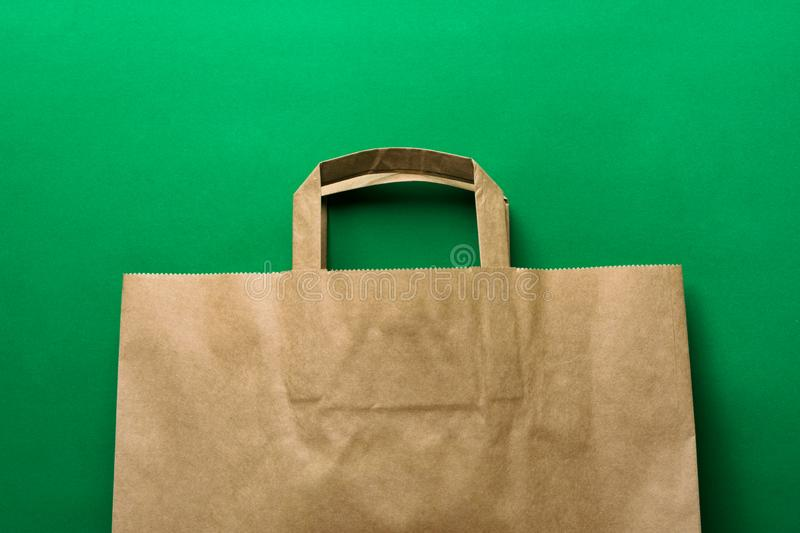 Brown kraft paper grocery shopping bag on green background. Plastic-free alternatives environmental protection nature friendly. Living. Mockup with copy space stock photo