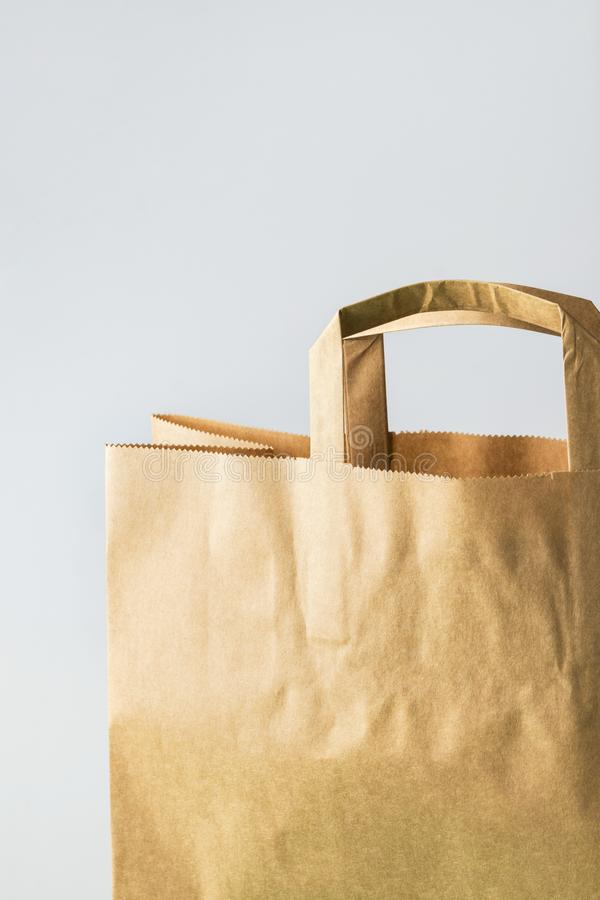 Brown kraft paper grocery shopping bag on white wall background. Plastic-free alternatives environmental protection. Nature friendly living. Mockup with copy stock images