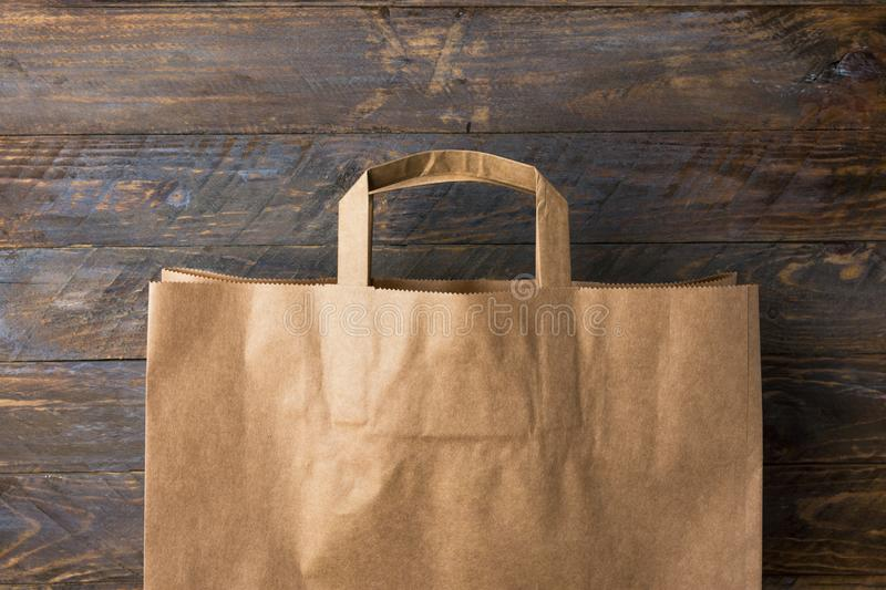 Brown kraft paper grocery shopping bag on wooden background. Plastic-free alternatives zero waste environmental protection. Nature friendly living. Mockup with stock photo