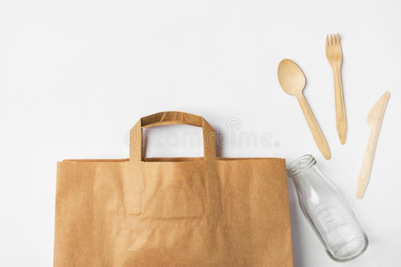 Brown Kraft paper grocery shopping bag wooden flatware cutlery on white background. Plastic-free alternatives zero waste. Environmental protection nature stock photos