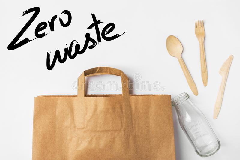 Brown Kraft paper grocery shopping bag wooden flatware cutlery on white background. Plastic-free alternatives zero waste. Environmental protection eco friendly stock image