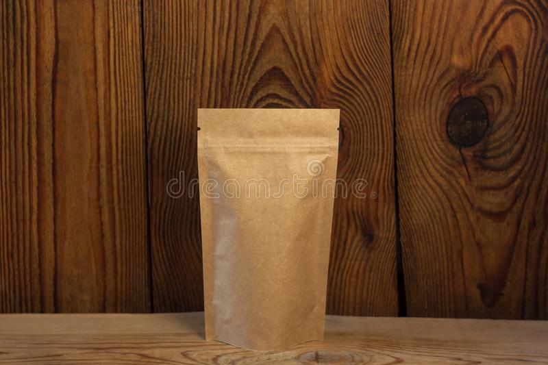 Brown kraft paper pouch bags with coffee beans front view on a wooden background. Packaging for foods and goods. Template mock-up. Packs with clasps and windows stock image