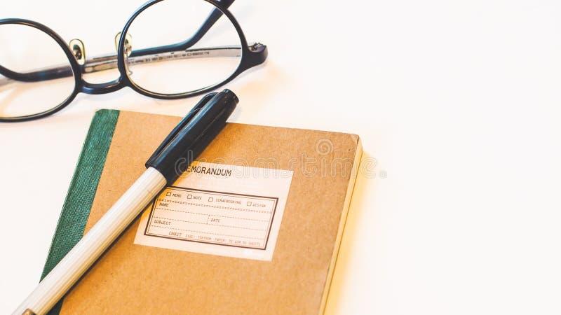 Brown-Kraftpapierabdeckungsnotizbuch mit Stift und Brillen lokalisiertem weißem Hintergrund lizenzfreie stockbilder
