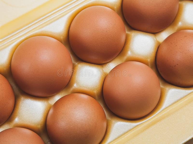 Brown large chicken eggs in yellow packaging. Close-up royalty free stock photos