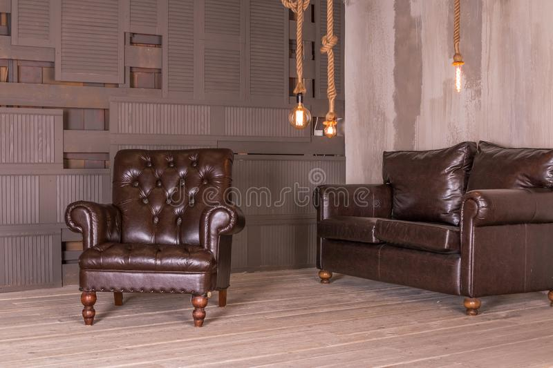 Brown leather armchair and vintage leather sofa. interior composition.retro furniture. Creative design. Copy space royalty free stock photography