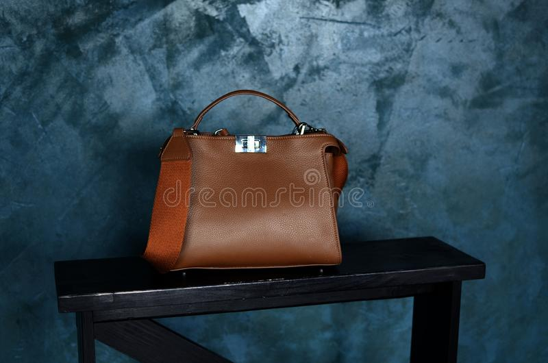 Brown leather bag for business man with mockup metal decorative fastener on grey textured cement surface, conctere wall stock photo