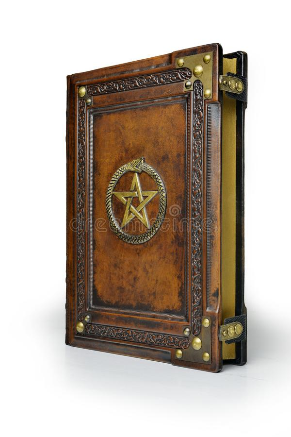 Brown leather book cover with gilded pentagram and the Ouroboros symbol, surrounded with deeply embossed frame and metal corners -. Captured stand up from the stock photography