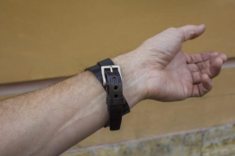 Brown leather bracelet with a buckle on a left man`s hand. A brown leather bracelet with a buckle on a left man`s hand stock photo
